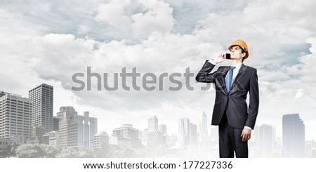 Young man engineer in helmet talking on mobile phone - stock photo