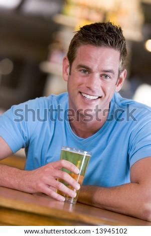Young man enjoying a beer at a bar - stock photo