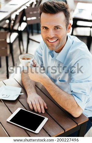 Young man enjoying a coffee over his tablet - stock photo