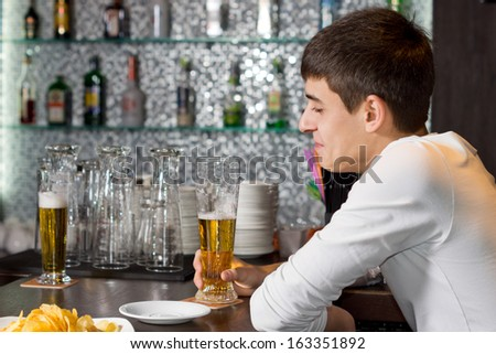 Young man enjoying a glass of beer with a friend as he sits at a table or counter in a bar or club