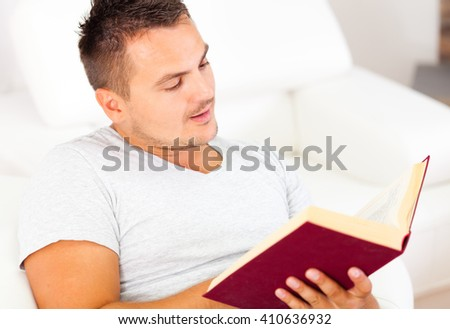 Young man enjoying a thick red book - stock photo
