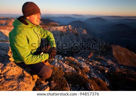 Young man enjoying autumn mountain sunset - stock photo