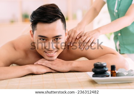 Young man enjoying back massage in spa center - stock photo