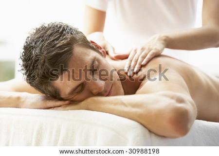 Young Man Enjoying Massage At Spa - stock photo