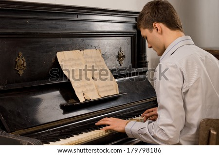 Young man enjoying playing an old nostalgic melody as he sits at an upright piano reading an old music score - stock photo