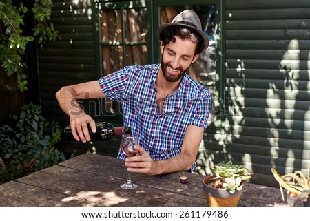 young man enjoying red wine outdoors in summer spring season backyard garden at home - stock photo