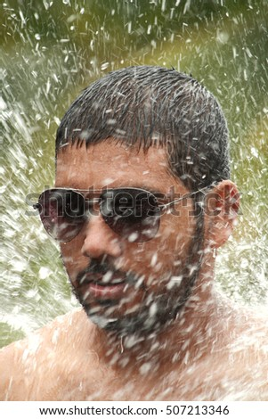 Young man enjoys in a water splash