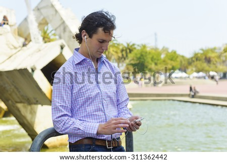 young man enjoys information, music, and information on the go. - stock photo