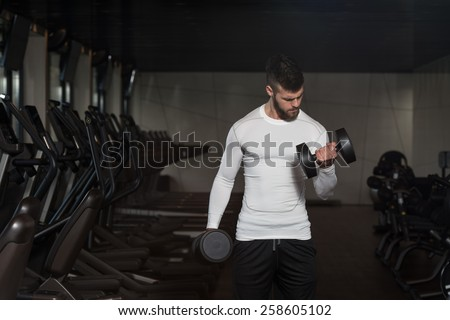 Young Man Exercise Biceps With Dumbbells - Dumbbell Concentration Curls - stock photo