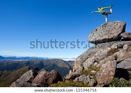 Young man exercises yoga in the mountains - stock photo
