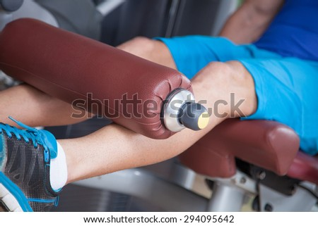 Young man exercising in gym, using machine - stock photo