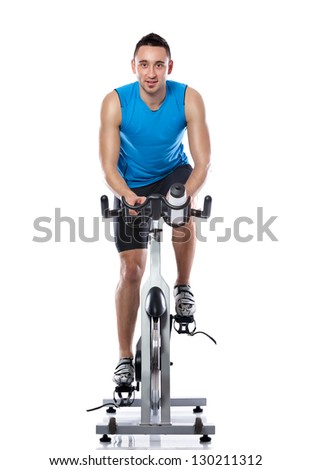 Young man exercising on a bike,  spinning exercise class - stock photo