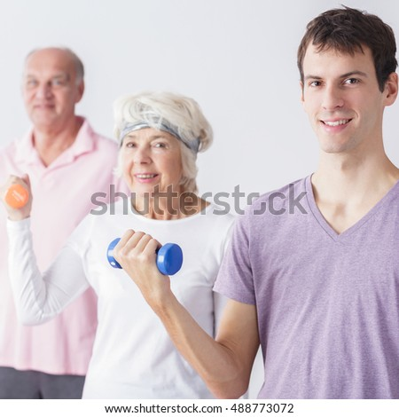 Young man exercising with active happy seniors