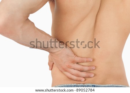 Young man experiencing back pain against a white background