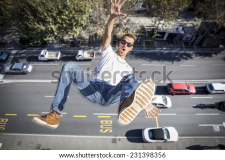 young man falling down of a building - stock photo