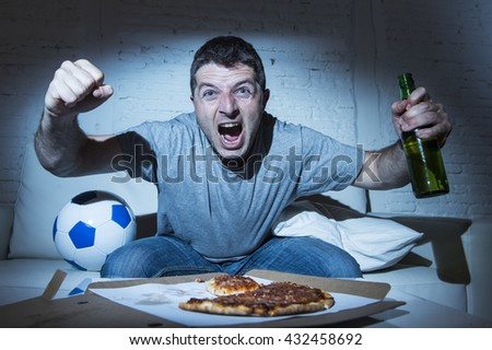 young man fanatic and crazy football fan watching television soccer match alone screaming happy celebrating scoring goal in glad and ecstatic face expression with beer bottle and pizza - stock photo