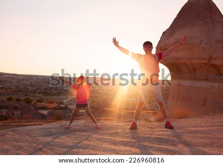 Young man father dad with little daughter kid child standing with raised hands on top of a mountain and meeting sunset in Cappadocia Turkey - stock photo