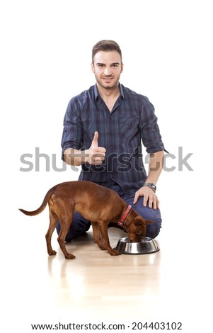 Young man feeding his dog and shows thumbs up - stock photo