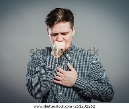 Young man feeling sick and taking a pill - stock photo