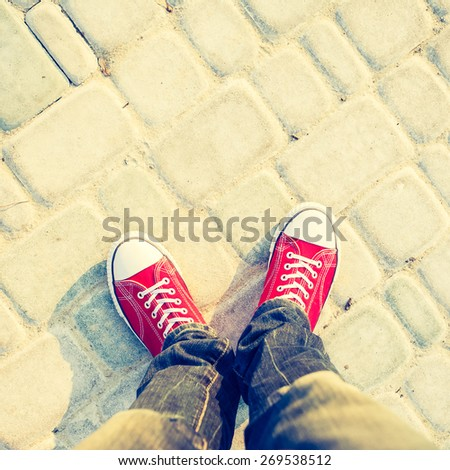 young man feet in red sneakers on cobbled road  - stock photo