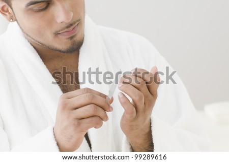stock-photo-young-man-filing-his-nails-9