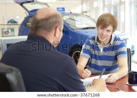 Young man filling in paperwork in car showroom - stock photo