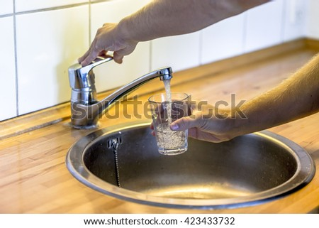 Young man filling up a glass with water in the sink in kitchen at home. - stock photo