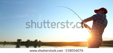 Young man fishing at sunset - stock photo