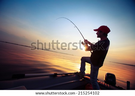 Young man fishing from the boat at sunset - stock photo