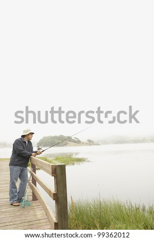 Young man fishing off a pier - stock photo