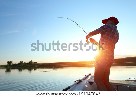 Young man fishing on a lake from the boat at sunset - stock photo
