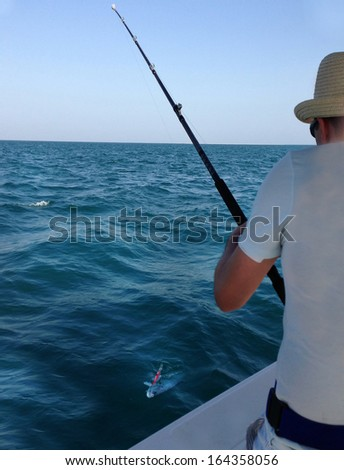 Young man fishing on a ocean. Catching big Queen fish