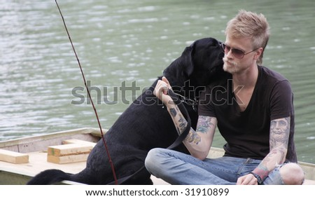 Young man fishing with his dog. - stock photo