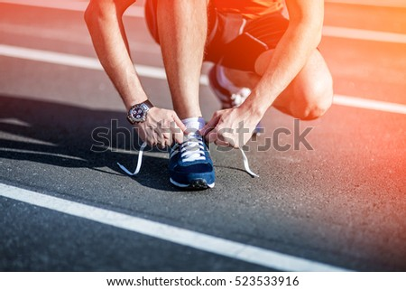Young Man Fitness Runner tying his shoes on a running track. Shoelaces, Urban jogger