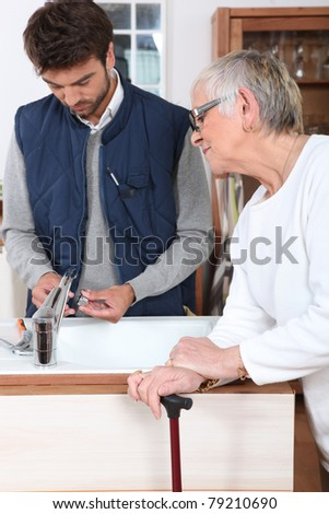 young man fixing faucet for older woman - stock photo