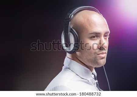 Young man focused on music black background - stock photo