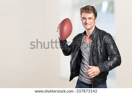 Young man football player portrait holding american football - stock photo