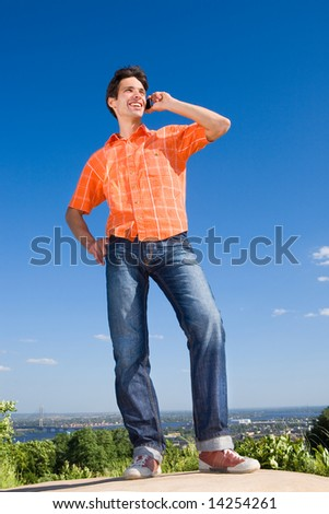 Young man from the phone calls. It was on Mount. Against a blue sky with clouds - stock photo