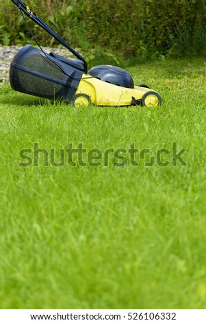 Young man gardener using lawn mower at sunny day