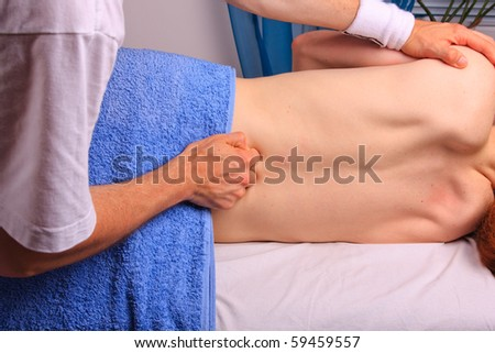 Young man gets back massage - stock photo