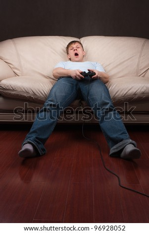 young man gets tired while playing video games on gray background - stock photo