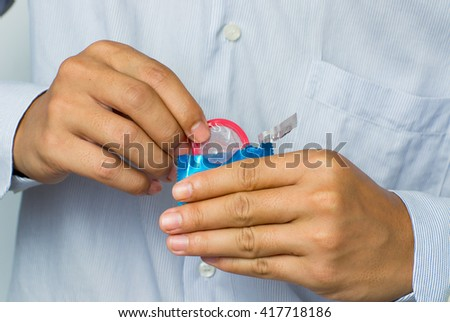 Young man giving condom - stock photo