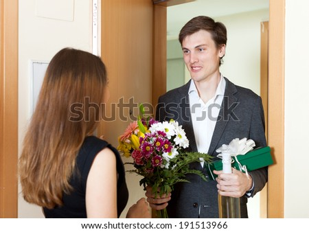 Young man giving gifts to woman at home door