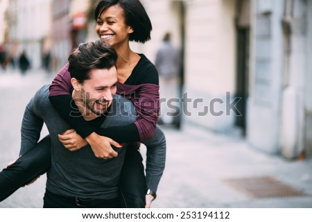 Young man giving girlfirend piggyback ride