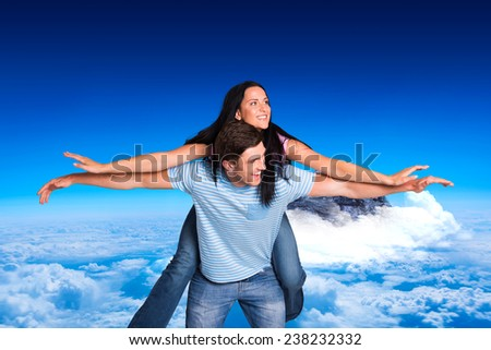 Young man giving girlfriend a piggyback ride against mountain peak through the clouds - stock photo