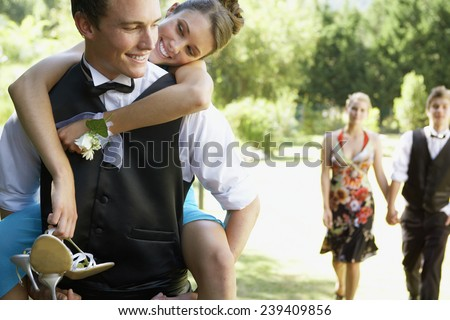 Young Man Giving His Date a Piggyback Ride - stock photo