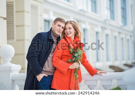 Young man giving his girlfriend a rose and kissing celebrating valentines day. Young couple in love outdoor.Stunning sensual outdoor portrait of young stylish fashion couple posing in park - stock photo
