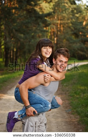 Young man giving piggyback ride to woman