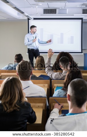 Young man giving speech in lecture hall for a group of students