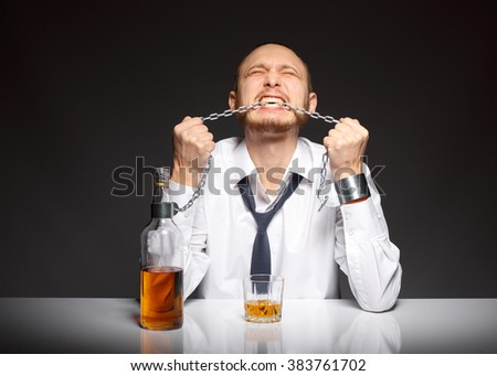Young man gnaws chain, depending on the habits of alcohol - stock photo